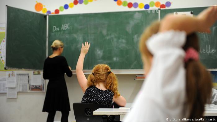 A teacher writes in German on a blackboard