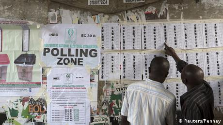 Two men point to voting lists hung up on a wall next to a poster that reads 'polling zone'