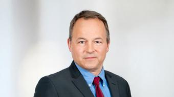 Photo of Claus Stäcker wearing a suit and tie