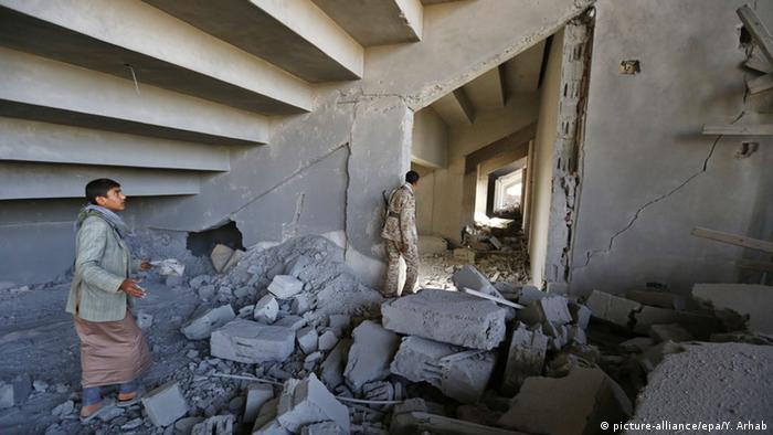 epa04701802 A member of the Houthi militia and a young Yemeni walk among the ruins of a stadium allegedly destroyed by a Saudi airstrike on Sana'a, Yemen, 12 April 2015. EPA/YAHYA ARHAB +++(c) dpa - Bildfunk+++