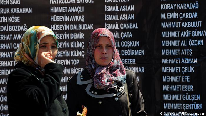 Faciada hayatını kaybedenlerin yakınları, madencilerin adını taşıyan bir anıtın önünde duruyor