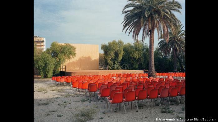 Foto von einer Leinwand hinter roten Stühlen und einer Palme (Foto: Wim Wenders/Courtesy Blain/Southern)