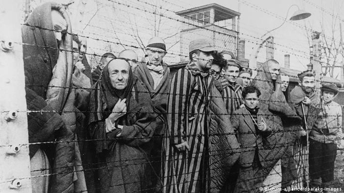 Haggard prisoners stand huddled behind barbed wire in a Holocaust concentration camp (picture-alliance/dpa/akg-images)