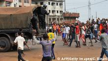 Guinean riot police truck drives past opposition suporters on April 13, 2015 in Conakry. Several protesters were wounded on April 13 as Guinean police opened fire during violent demonstrations across the capital Conakry against the regime of President Alpha Conde. AFP PHOTO / CELLOU BINANI (Photo credit should read CELLOU BINANI/AFP/Getty Images)