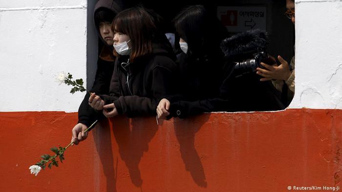Angehörige werfen am Jahrestag des Fährunglücks Rosen ins Meer (Foto: Reuters)