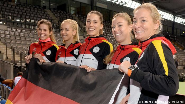 Germany's Fed Cup team holds a flag with their captain Barbara Rittner