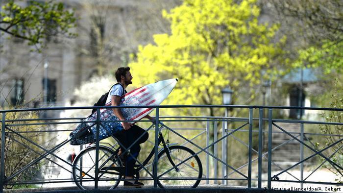 A man with a surfboard in Munich's Englischen Garten