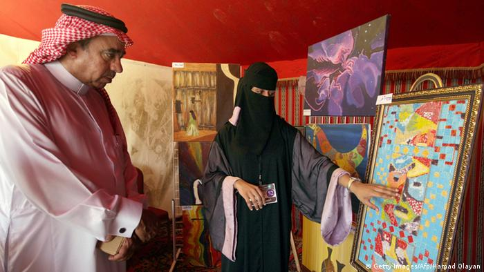 A veiled woman shows a man her artwork in Saudi Arabia