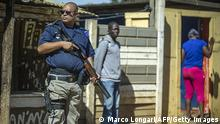 16. April 2015 An armed South African police officer stands guard as foreign nationals pack up their shops in the small village of Primrose, near Germiston about 15kms east of Johannesburg, on April 16, 2015, after anti-immigrant violence in Durban left six people dead and spread to the economic capital Johannesburg. In the past two weeks, shops and homes owned by Somalis, Ethiopians, Malawians and other immigrants in Durban and surrounding townships have been targeted, forcing families to flee to camps protected by armed guards. AFP PHOTO / MUJAHID SAFODIEN (Photo credit should read MUJAHID SAFODIEN/AFP/Getty Images)