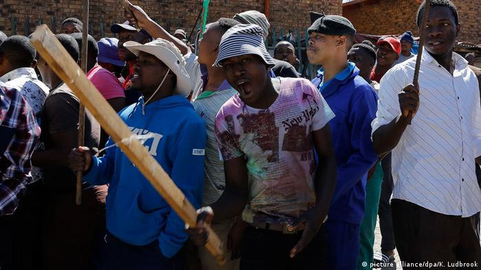 Local South African men carry clubs as they call for foreign shop owners to leave the area during a wave of xenophobic violence