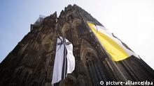 Eine Flagge mit einem Kreuz und Trauerflor weht am 16.04.2015 vor dem Dom in Köln (Nordrhein-Westfalen). Am 17.04.2015 findet hier der Trauergottesdienst für die Opfer des Absturzes des Germanwings Airbus in Frankreich statt. Foto: Rolf Vennenbernd/dpa +++(c) dpa - Bildfunk+++ (eingest. 17.4./fab)