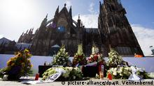 17.04.2015+++ Kränze liegen am 17.04.2015 auf dem Bahnhofsvorplatz vor dem Dom in Köln (Nordrhein-Westfalen), wo Menschen den Ökumenischen Gottesdienst für die Opfer des Absturzes der Germanwings-Maschine in Frankreich am 24. März auf einem großen Bildschirm verfolgen können. Foto: Rolf Vennenbernd/dpa