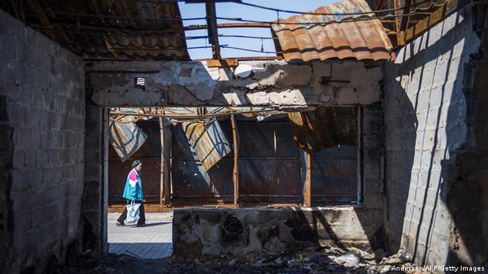 A woman carries her shopping past a burnt out market stall near the main station in April 2015 in Donetsk in eastern Ukraine.