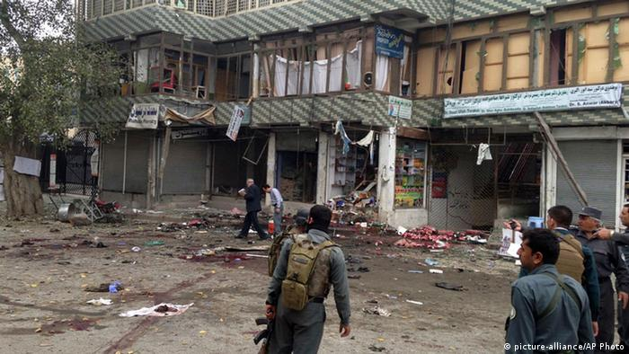 Afghan security forces inspect the site of a suicide attack near a bank branch in Jalalabad, east of Kabul, Afghanistan, Saturday, April 18, 2015 (AP Photo)