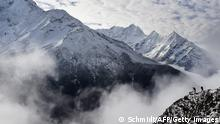 Bildunterschrift:Agence France-Presse reporter Ammu Kannampilly (2R), and Nepalese guide Pasang Sherpa (R) stand on a ridge over a valley leading north into the Khumbu region as they try to get a clear view of Mt. Everest on April 18, 2015. AFP PHOTO/ROBERTO SCHMIDT (Photo credit should read ROBERTO SCHMIDT/AFP/Getty Images)