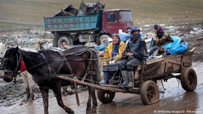 A Roma family drive a cart loaded with scrap metal in the outskirts of Cluj-Napoca