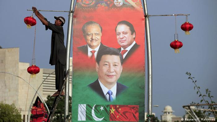A man hangs decorations on a pole next to a banner showing Pakistan's President Mamnoon Hussain (L), China's President Xi Jinping (C) and Pakistan's Prime Minister Nawaz Sharif, ahead of Xi's visit to Islamabad April 19, 2015 (Photo: REUTERS/Faisal Mahmood)