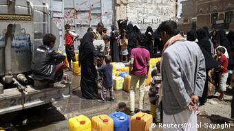 People fill containers with water from a water tanker