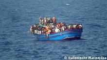 HANDOUT - Ein Foto herausgegeben am 30.06.2014 von der italienischen Marine zeigt ein Boot mit Flüchtlingen am 29.06.2014 auf dem Mittelmeer zwischen Sizilien und Nordafrika. Am Wochenende rettete die Marine im Mittelmeer innerhalb von 48 Stunden mehr als 5000 Migranten - so viele wie nie zuvor. Für 30 Menschen endet die Überfahrt tödlich, sie ersticken vermutlich an Bord ihres voll besetzten Bootes. Foto: Italienische Marine/dpa (ACHTUNG: Nur zur redaktionellen Verwendung und bei der vollständigen Nennung der Quelle)