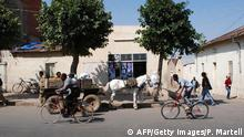 People using bicycles and horses make their way in a street of the Eritrean capital Asmara on November 3, 2007. The red and blue logo of US-government food aid is a common sight in Eritrea. Donated grain sacks are re-stitched as popular shopping bags, while cooking oil tins bloom with colourful flowers on window sills. Any food inside, however, has long gone. This fiercely independent Horn of Africa country ended free distribution of food aid in 2005 after illegally seizing thousands of tonnes of grain, saying it was determined to feed itself without outside help. AFP PHOTO/Peter MARTELL (Photo credit should read PETER MARTELL/AFP/Getty Images)