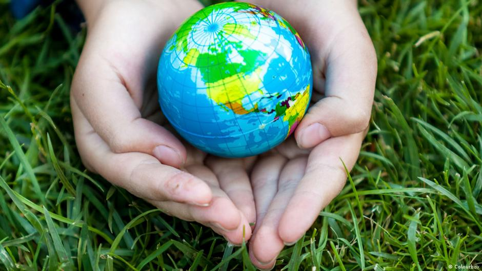 Young girl holding Earth in hands against green grass (Photo: Colourbox)