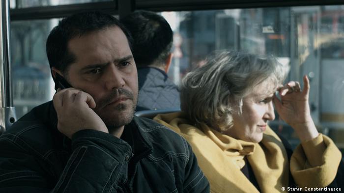 Ein Mann telefoniert im Bus mit dem Handy, neben ihm schaut eine Frau weg