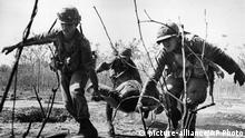 Dashing low under enemy sniper fire, U.S. infantrymen carry wounded comrade from the battlefront near Cu Chi, South Vietnam, Feb. 14, 1966. Elements of the U.S. 25th division met heavy Viet Cong resistance when they initiated action to expand the division's perimeter. (AP Photo)