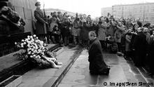 Black and white photo of Willy Brandt' kneeling before the wreath at the memorial with photographers crowding in to capture the moment
