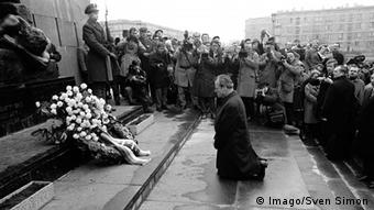 Pessoa de joelhos diante de coroa de flores, cercada por fotógrafos