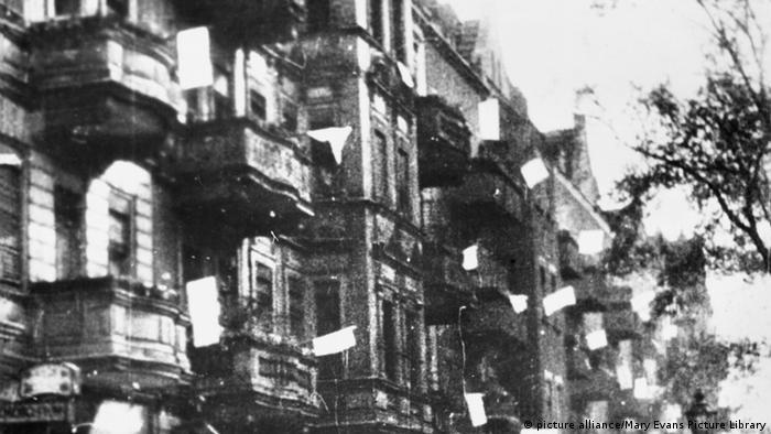 Prédio antigo em que bandeiras brancas acenam das janelas