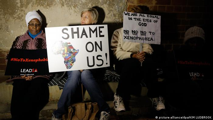 Three South Africans sit holding placards to protest xenophobia
