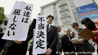 Lawyers representing local residents seeking an injunction to stop the restart of two reactors at Kyushu Electric Power Co.'s Sendai nuclear plant in southwestern Japan stand with banners criticizing a court decision to dismiss the demand on April 22, 2015, in front of the Kagoshima District Court (Kyodo)