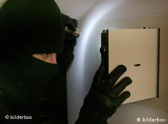 A thief wearing a balaclava opens a wall safe