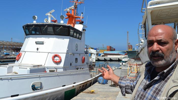 A Libyan coast guard points towards a broken down boat.