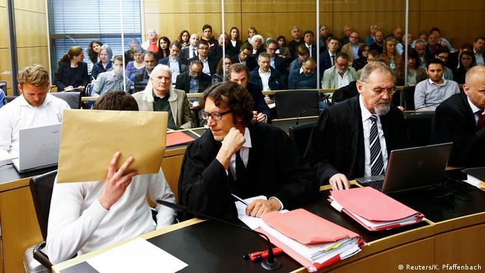 Der Angeklagte Sanel M. (l) verbirgt im Gerichtssaal sein Gesicht hinter einem braunen Umschlag, Foto: Kai Pfaffenbach/Reuters