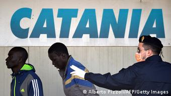 official pushes two black men Forward; sign reading Catania in the background