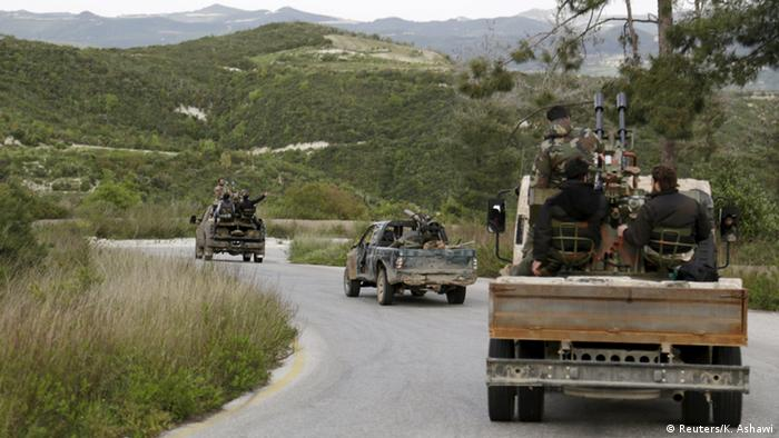 Rebel fighters drive in a convoy toward the northwestern town of Jisr al-Shughour