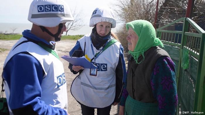 Наблюдатели ОБСЕ в белых касках и пожилая жительница Широкино
