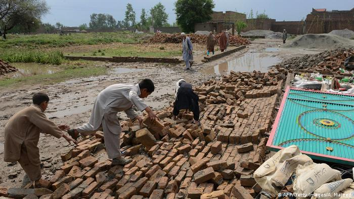 Residents collect bricks after their house collapsed following heavy rain and winds in Peshawar, Pakistan in April, 2015
