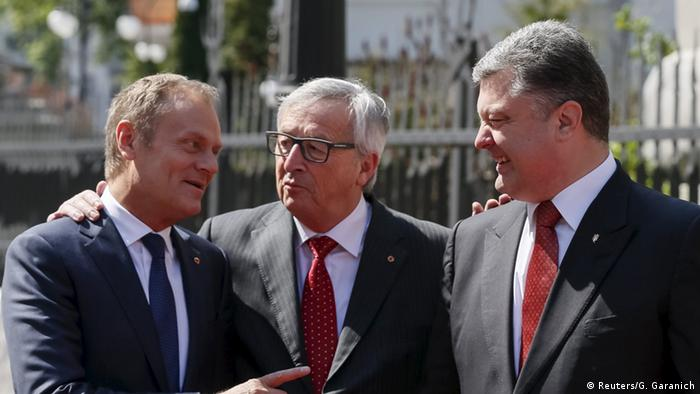European Council President Donald Tusk gestures as he talks to European Commission President Jean Claude Juncker and Ukrainian President Petro Poroshenko before their meeting in Kiev April 27, 2015.