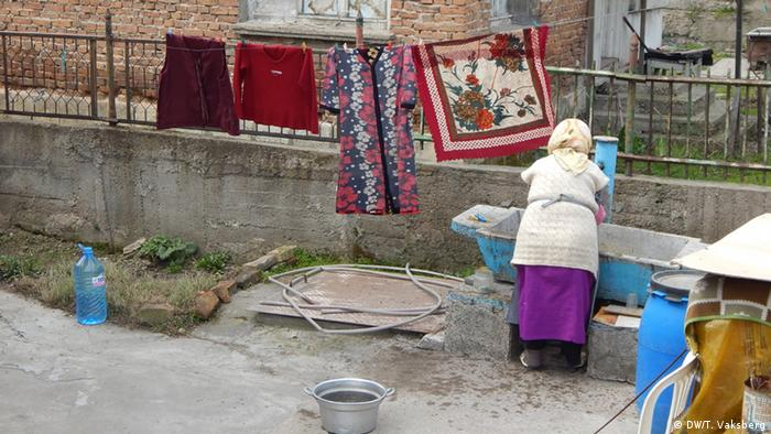 A woman does washing in the Roma settlement in Vidin