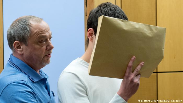 Der Angeklagte Sanel M. (r) wird am 24.04.2015 zu Verhandlungsbeginn in einen Sicherheitssaal des Landgerichts in Darmstadt (Hessen) geführt und verbirgt sein Gesicht hinter einem braunen Umschlag, Foto: Boris Roessler/dpa