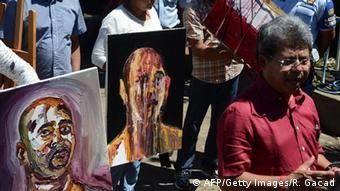 Indonesian lawyer Todung Mulya Lubis (R) displays recent paintings done in prison by Australian drug convict and death row prisoner Myuran Sukumaran at the Nusakambangan port in Cilacap across from the Nusakambangan maximum security prison island on April 28, 2015 (Photo: ROMEO GACAD/AFP/Getty Images)