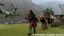 28.04.2015+++ A Nepalese resident injured in an earthquake (L) is carried by a relative towards an Indian Army helicopter as others follow at Lapu in Gorkha on April 28, 2015. Rescuers in Nepal battled April 28, 2015 to reach remote communities devastated by a huge earthquake that has killed at least 4,349 people, as the impoverished country's leader said relief workers had still not reached many of the worst-hit areas. AFP PHOTO / SAJJAD HUSSAIN (Photo credit should read SAJJAD HUSSAIN/AFP/Getty Images)