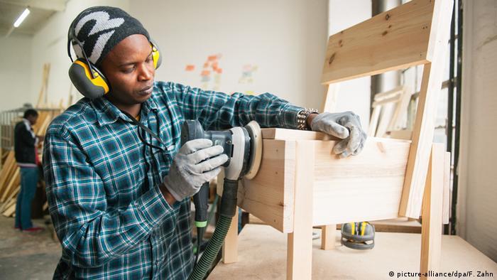 Ein junger Flüchtling bearbeitet in einer Werkstatt eine Holzbank.