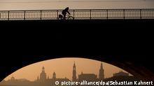 Ein Radfahrer fährt am 16.02.2015 bei Sonnenaufgang in Dresden (Sachsen) vor der Dresdner Stadtsilhouette mit der Kuppel der Kunstakademie (l-r), der Hochschule für Bildende Künste, der Frauenkirche, dem Ständehaus, der katholischen Hofkirche, dem Schlossturm und der Semperoper über die Marienbrücke. Foto: Sebastian Kahnert/dpa +++(c) dpa - Bildfunk+++ .Wetter; .Architektur; .lsn; Tourismus; Geografie; Städte; Architektur; Wetter; Türme; Bauten; Dämmerung; architecture; buildings; twilight; dusk; geography; towns; cities; tourism; towers; weather; Weather:WEA