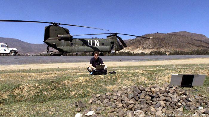 Der Pressefotograf Jasper Juinen sitzt in Eritrea vor einem Hubschrauber der Vereinten Nationen. (Foto: picture-alliance/dpa/J. Juinen)