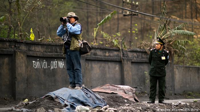 Ein Pressefotograf steht auf einem Schuttberg. Ein vietnamesischer Soldat beobachtet ihn. (Foto: picture alliance/ZB/A. Burgi)