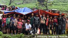 28.04.2015+++ Nepalese villagers shelter from rain under foam and plastic sheets as an Indian Army helicopter delivers aid following an earthquake at Lapu in Gorkha on April 28, 2015. Rescuers in Nepal battled April 28, 2015 to reach remote communities devastated by a huge earthquake that has killed at least 4,349 people, as the impoverished country's leader said relief workers had still not reached many of the worst-hit areas. AFP PHOTO / SAJJAD HUSSAIN (Photo credit should read SAJJAD HUSSAIN/AFP/Getty Images)