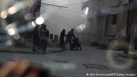In der syrischen Stadt Duron laufen Menschen über eine Straße. Sie ist ganz nebelig und die Häuser sind zerstört. (Foto: Abd Doumany/AFP/Getty Images)